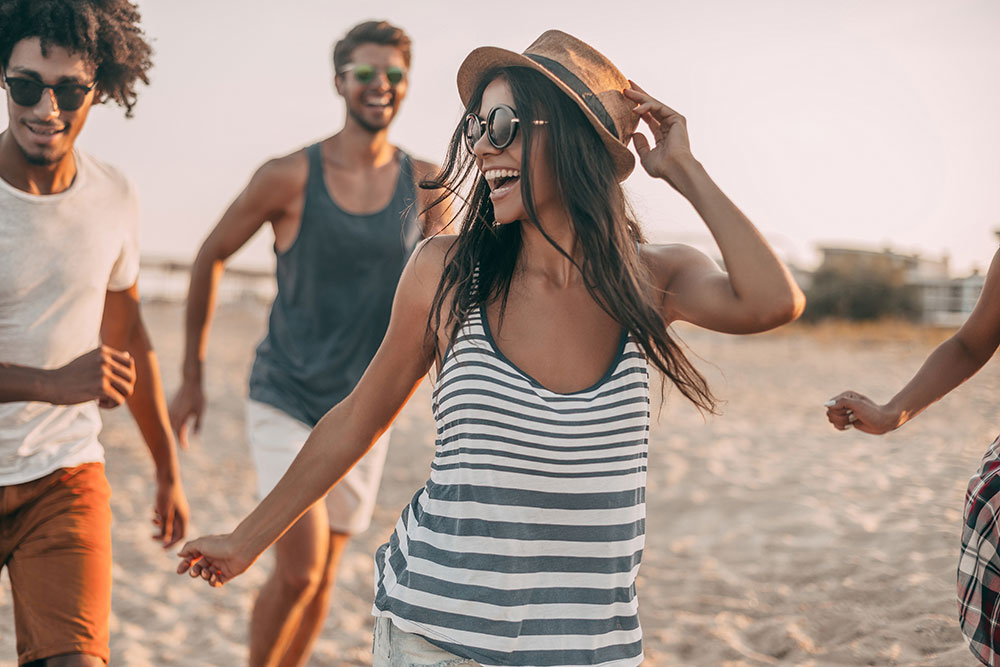 woman running on the beach with her friends smiling and having fun